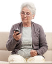 Surprised senior woman talking at cellphone staying on couch and looking text message or video chat on isolated on white Stock Images