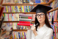Surprised  Student with Graduation Cap Holding Books Royalty Free Stock Photo