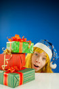 Surprised teen girl looking from behind presents Stock Photography