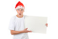 Surprised teenager with white board in santa s hat holds isolated on the background Stock Photography