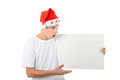 Surprised teenager with white board in santa s hat holds isolated on the background Stock Image