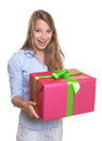Surprised woman with a christmas gift attractive young long blond hair and in her hands on white background Royalty Free Stock Photography