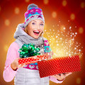 Surprised woman with a christmas gift with magic shining from b photo of happy box over night lights Royalty Free Stock Photos