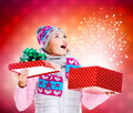 Surprised woman with a christmas gift with magic shining from b photo of happy box over night lights Stock Photography