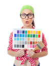 Surprised woman holding paintbrush and color samples Royalty Free Stock Photo