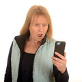 Surprised woman with mobile looking at message on telephone white background Stock Image