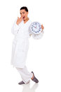 Surprised woman pajamas portrait of young in with clock Stock Photography
