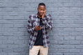 Surprised young african guy looking at cell phone Royalty Free Stock Photo