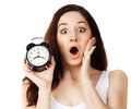 Surprised young brunette woman holding clock Royalty Free Stock Photography