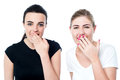Surprised young girls laughing out loud we are shocked in amusement to hear this news Stock Image