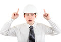 Surprised young man in hard hat pointing his fingers up isolated on the white Royalty Free Stock Image