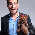 Surprised young man holds puppy casual holding a and looking into the camera on gray background Stock Image