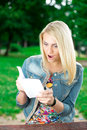 Surprised young woman with book in park portrait of beautiful on green background of city Stock Photo