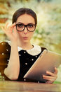 Surprised young woman with glasses and tablet beautiful expression holds a computer Royalty Free Stock Photo