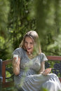 Surprised young woman reading text message on smart phone in park Stock Photo