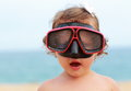 Surprising baby girl in diving mask looking fun on blue sea background Royalty Free Stock Photos