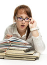Surprising unexpectedness the girl sits at books and is surprised looks Stock Image