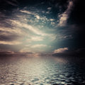 Surreal dark clouds reflected in water surface color toned image Royalty Free Stock Photography