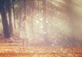 Surreal photo of young woman standing in forest. image is textured and toned. dreamy concept Royalty Free Stock Photo