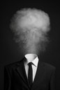 Surrealism and business topic: the smoke instead of a head man in a black suit on a dark background in the studio Royalty Free Stock Photo