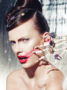 Surrealistic fashion portrait of a woman wearing jewellery young beautiful with dramatic makeup and holding skeleton hand Stock Image