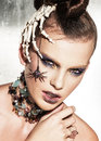 Surrealistic fashion portrait of woman young beautiful with dramatic makeup wearing jewellery and holding a skeleton hand Royalty Free Stock Photos