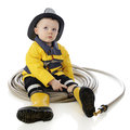 Surrounded by hose an adorable baby fireman sits in a circle of on a white background Stock Photo