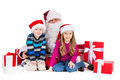 Surrounded by many present isolated over white background old santa claus in red costume sitting together with two little kids Royalty Free Stock Image