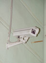 A surveillance camera on the wall on the street