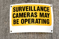 Surveillance cameras sign in the street reads may be operating concept photo of security crime criminality Stock Photos