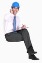 Surveyor sitting on an invisible stool and talking his mobile phone Stock Photography