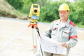 Surveyor works with theodolite one worker working transit equipment at road construction site outdoors Stock Photo