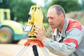 Surveyor works with theodolite one worker working transit equipment at road construction site outdoors Royalty Free Stock Photo