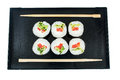 Sushi on a black wooden tray with chopsticks isolated Royalty Free Stock Photo
