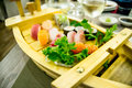 Sushi boat with variety of sushi pieces with green salad