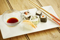 Sushi with chopsticks assorted on white dish and wooden table top Royalty Free Stock Photo