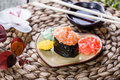 Sushi Gunkan maki with salmon on plate on bamboo mat decorated with flowers. Japanese cuisine. Selective focus. Royalty Free Stock Photo
