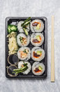 Sushi menu in black transportbox or bento box on gray background, top view, close up