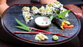 Sushi nicely decorated presentation of on a black serving plate Stock Photography