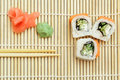 Sushi roll on bamboo mat pieces of Stock Images