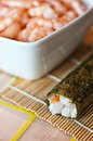 Sushi roll and bowl of shrimp still life on bamboo mat a white pyrex full Royalty Free Stock Photo