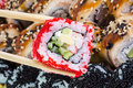 Sushi roll with red tobiko and canada sushi roll with sesame in chopsticks black Royalty Free Stock Images