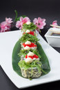 Sushi roll in tempura isolated on blask background and put on white dish and decorated with bamboo list salad chuka and soy sauce Royalty Free Stock Photography