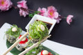 Sushi roll in tempura isolated on blask background and put on white dish and decorated with bamboo list salad chuka and soy sauce Royalty Free Stock Images