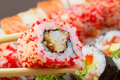 Sushi roll in tempura and red tobiko warm with sliced chopsticks on made dish background Royalty Free Stock Photo