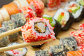 Sushi roll in tempura and red tobiko warm with sliced chopsticks on made dish background Stock Photography