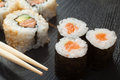 Sushi rolls on black plate and chopsticks assortment wooden Stock Photos