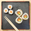 Sushi rolls on black plate and chopsticks assortment wooden top view Stock Photos