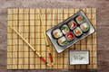 Sushi rolls on a plate on bamboo brown straw mat  with chopsticks close up Royalty Free Stock Photo
