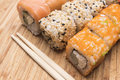 Sushi rolls with salmon, red caviar, sesame and sushi sticks, close-up view Royalty Free Stock Photo